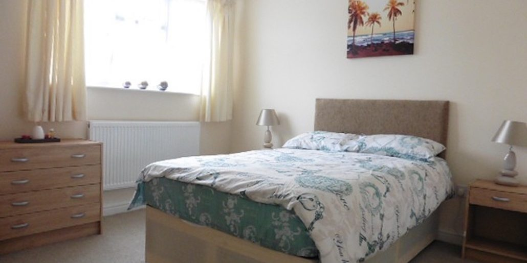 double bed in a large bedroom with palm trees as a picture