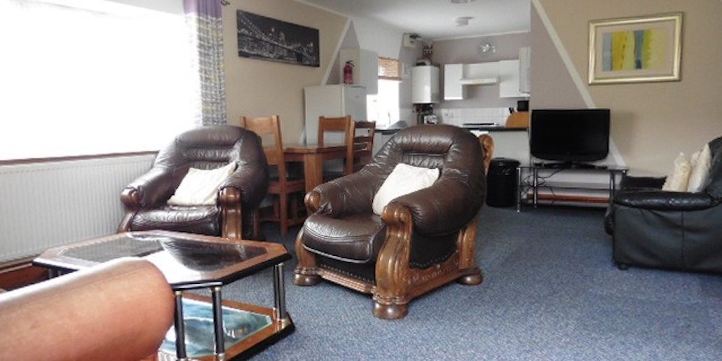 2 arm chairs in a open lounge with a kitchen area