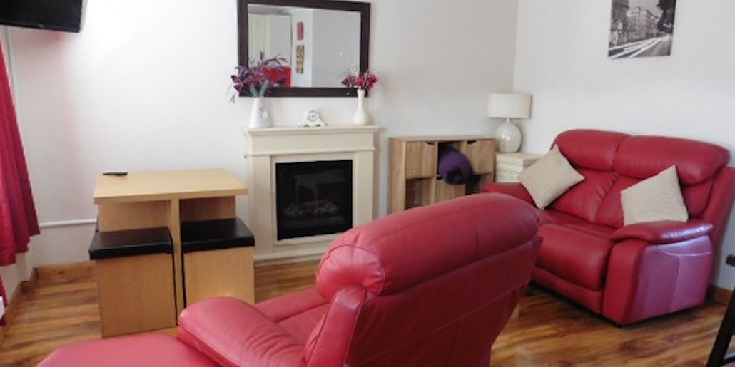 red sofa in a front room with a small tv