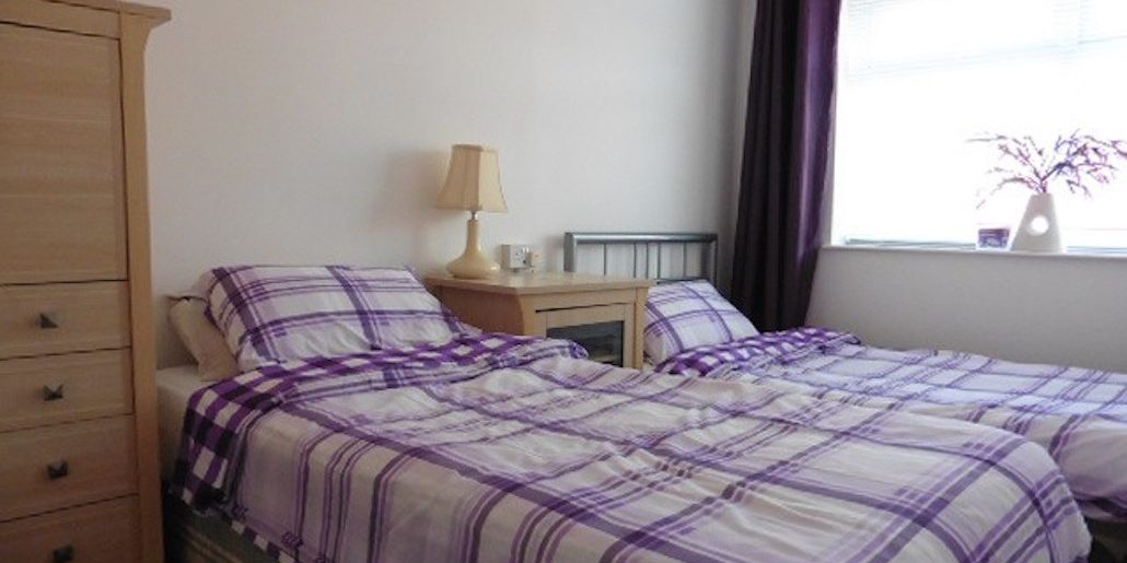 inside bedroom of checked quilt in purple