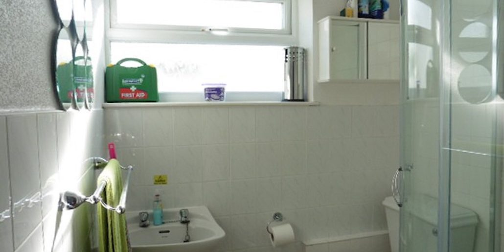 white bathroom with green towels