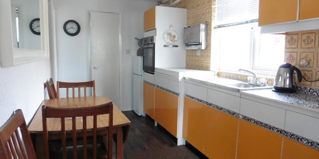 orange kitchen with a dining table and chairs