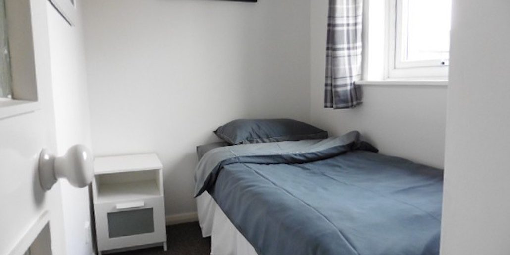 single bedroom with dark bedding and checked curtains