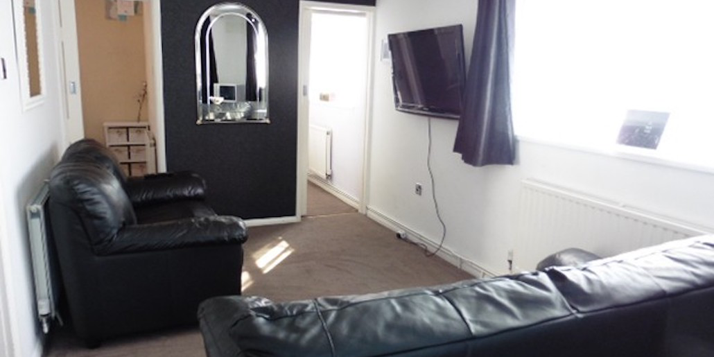 black sofa, with tv on the wall, chalet lhs 18 at Leysdown Holidays, at Leysdown on Sea, Kent